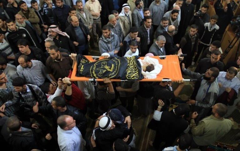 Palestinian mourners carry the body of Ranan Arafat, 4, during her funeral in Gaza City. At least 100 have been wounded, according to medical officials.