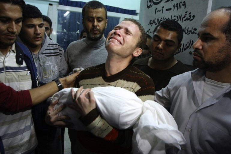 Jihad Masharawi weeps while he holds the body of his 11-month old son Ahmad, at Shifa hospital following an Israeli air strike on their family house, in Gaza City. The Israeli military said its assassination of the Hamas military commander Ahmed Jabari marks the beginning of an operation against Gaza fighters.
