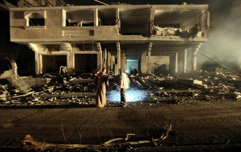 Palestinians inspect their home next to a destroyed Hamas site.