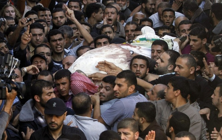 Palestinian mourners carry the body of Jabari during his funeral in Gaza City. At least 13 other Palestinians have been killed in recent fighting.