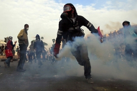 A protester runs as he returns a tear gas canister to riot police in Tahrir Square on Sunday [Reuters]