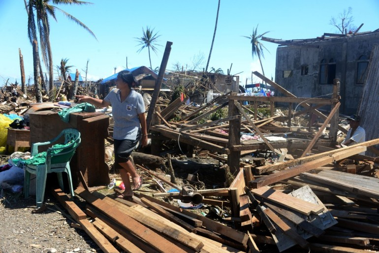 A woman looks for materials as she helps her husband rebuild their house in Cateel.