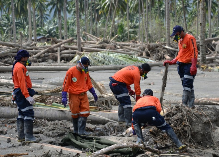 Rescuers dig up a body in New Bataan town. The typhoon has claimed over 1,000 lives, with many more believed to be dead.