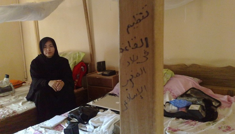 "The author at Ansar al Din(***)s guesthouse in Timbuktu. The graffiti says ""Al-Qaeda in the Islamic Maghreb""."