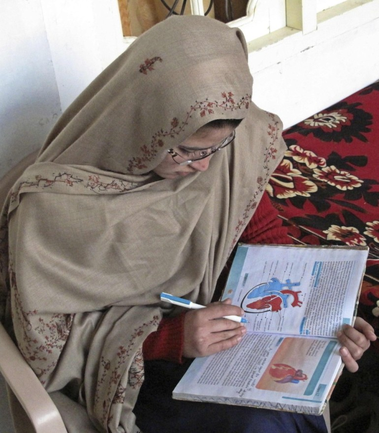 Kainat Riaz reads a book after returning from school at her home in Mingora, Swat valley. Two Pakistani girls shot by a Taliban hit squad trying to kill their classmate, Malala Yousufzai, returned to school on November 29, under tight security.