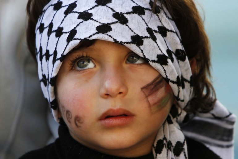 "A child in the West Bank city of Ramallah wears a keffiyeh during a rally supporting the change in the Palestinian Authority(***)s United Nations observer status from ""entity"" to ""non-member state""."