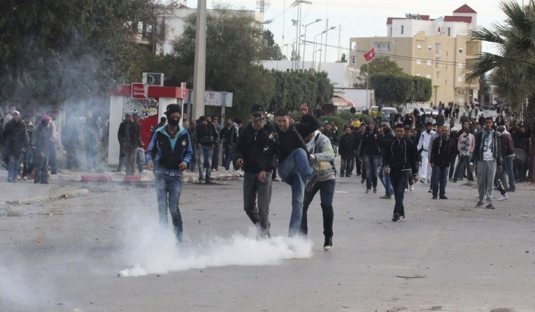 A protester kicks a tear gas canister back at police during clashes in Siliana, northwest of Tunis. Tunisian security forces dispersed several thousand protesters in the town that has seen days of clashes this week over economic problems.