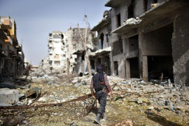 A fighter from the Islamist Syrian rebel group Jabhat al-Nusra walks among damaged houses in Aleppo [Reuters]