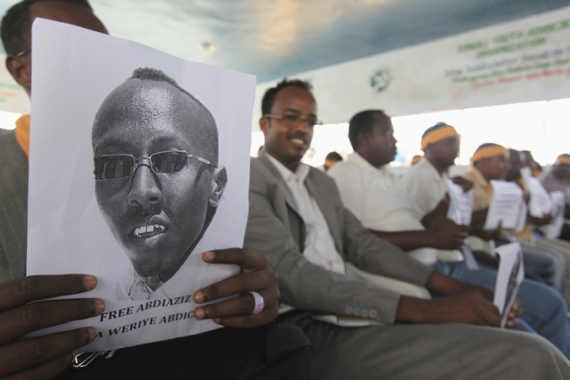 A Somali journalist holds a poster bearing the image of jailed reporter Abdiaziz Abdinur Ibrahim [Reuters]