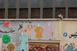 Graffiti in the vicinity of Tahrir Square illustrates Canal city figures, with arms and radio in hand, while traditional Port Saidi music has been popularised as wider segments of society [Sarah Mousa/Al Jazeera]