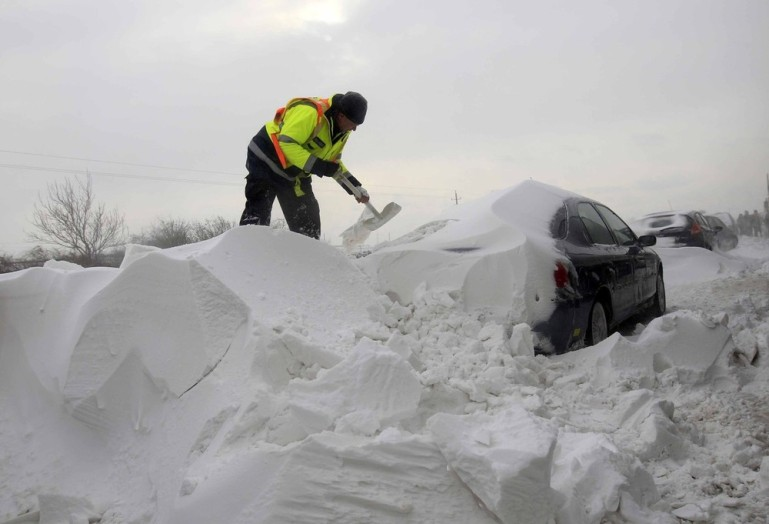 A member of the Hungarian rescue team removes snow from a car on the M1 highway, 80 km west of Budapest. Thousands of Hungarian motorists were trapped in heavy snow on the motorways.