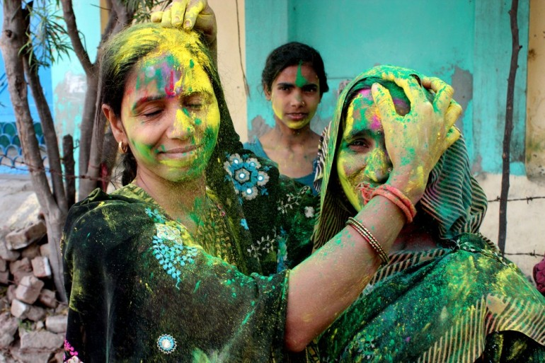 The festival of Holi is known for spirit of energy, unity and love. Two women apply color on each other during Holi celebrations.