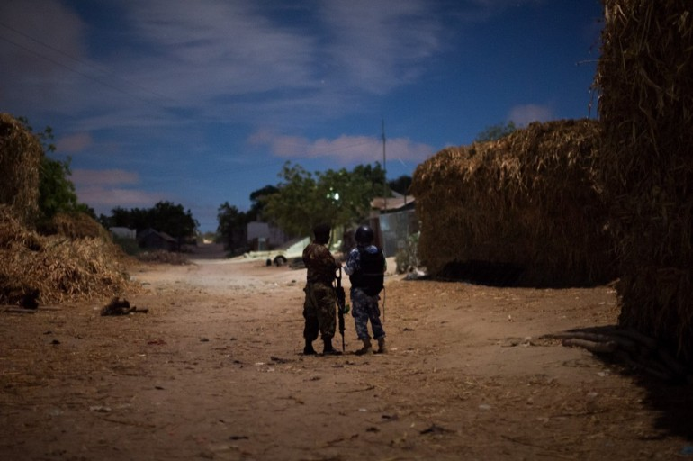 A Somali policeman stands with an AMISOM police officer in an outlying district of the capital at midnight. A new dawn is arriving in the city.