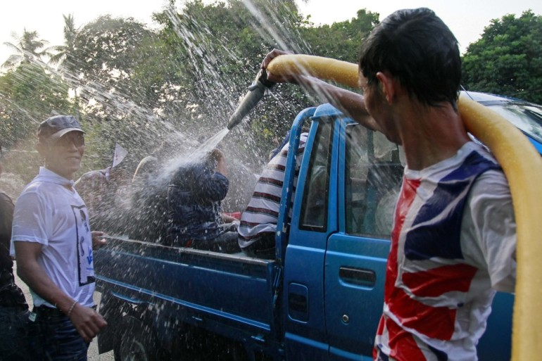 A man directs a water cannon to drench a passer-by. The festival is the most important holiday in Myanmar.