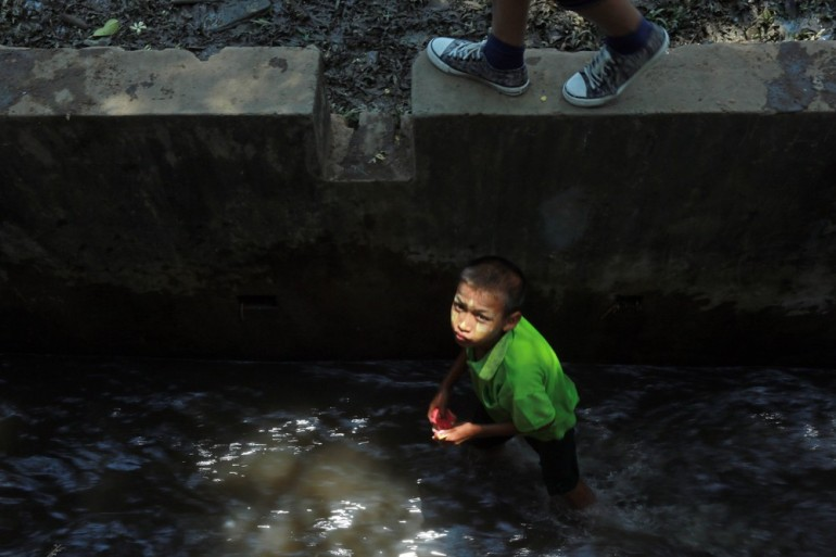A young boy collects bottles in a water drain canal, ostensibly to throw water on others.