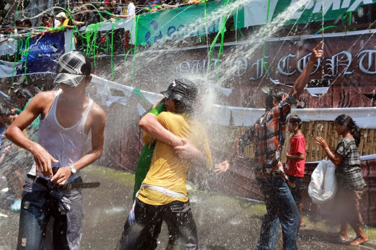 Revellers dance under water sprays and cannons.
