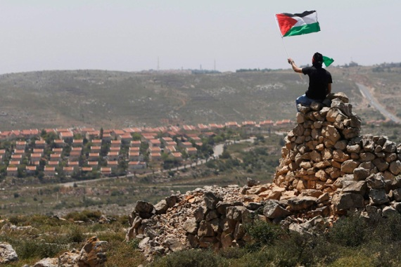A protester waves a Palestinian flag in front of the Jewish settlement of Ofra during clashes near the West Bank village of Deir Jarir near Ramallah on April 26, 2013 [File: Mohamed Torokman/Reuters]