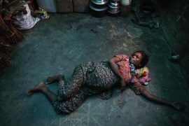 Nine-month pregnant Roma Hattu rolls around on the concrete floor, unable to afford medical attention [Reuters]