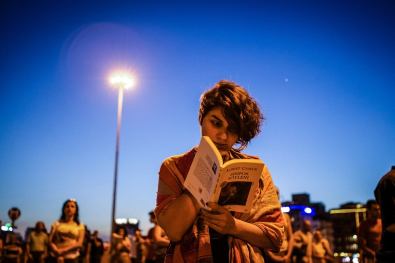 A woman reads the philosophical essay The Myth of Sisyphus by French author Albert Camus in Taksim Square. The book focuses on the search for meaning in the absence of God.