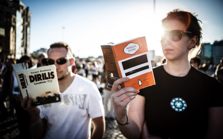 A man reads the Turkish book Resurrection Gallipoli 1915, written by Turgut Ozakman on the Battle of Gallipoli, while a woman beside him reads George Orwell(***)s Nineteen Eighty-Four.