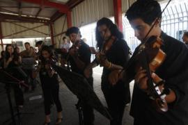 Members of Al Kamandjati project play instruments at the Qalandia checkpoint near the West Bank [Reuters]