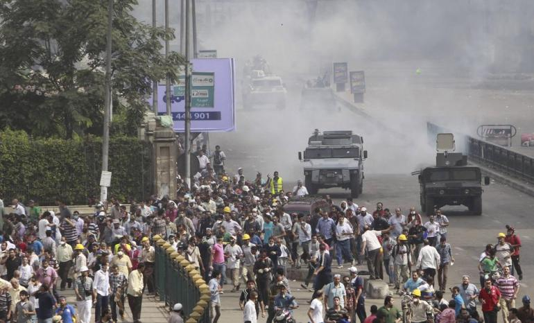 Members of the Muslim Brotherhood flee from tear gas and rubber bullets fired by riot police during clashes around Cairo University and Nahdet Misr Square.