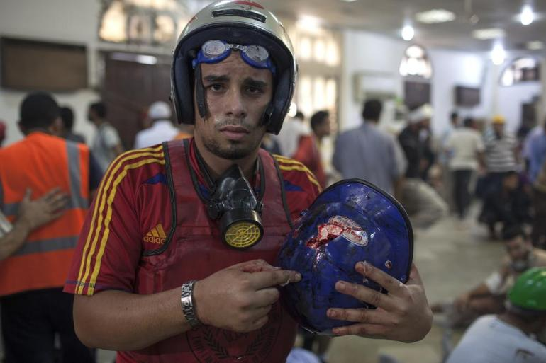 A pro-Morsi demonstrator holds the helmet of a protestor he says was shot dead earlier by police (a bullet hole and brain tissue was visible on the helmet) as he stands inside a packed field hospital.