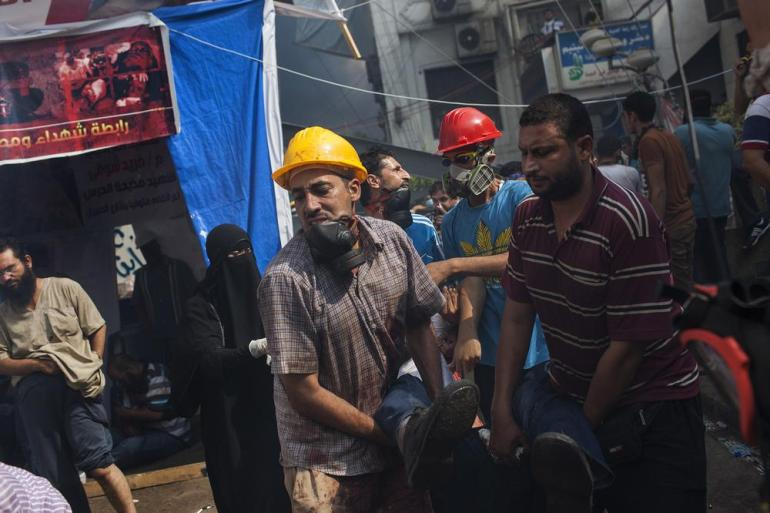 A wounded pro-Morsi supporter is taken by stretcher to a nearby field hospital inside the Rabaah al-Adawiya protest camp.