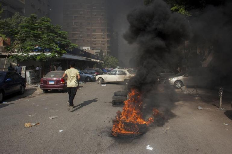 A man runs past burning tyres on the edge of the Rabaah al-Adawiya protest camp in Nasr City.