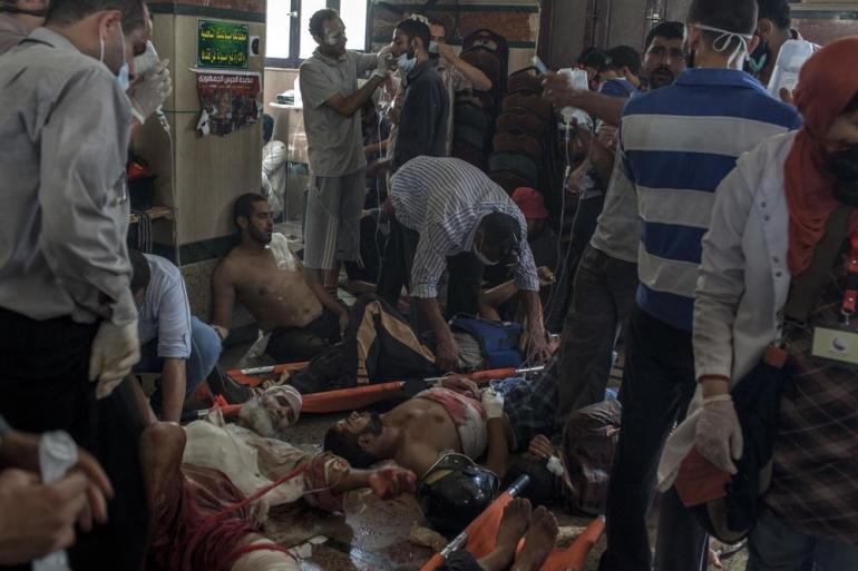 A stream of wounded people are treated by overwhelmed emergency staff inside a packed field hospital at the Rabaah al-Adawiya protest camp.