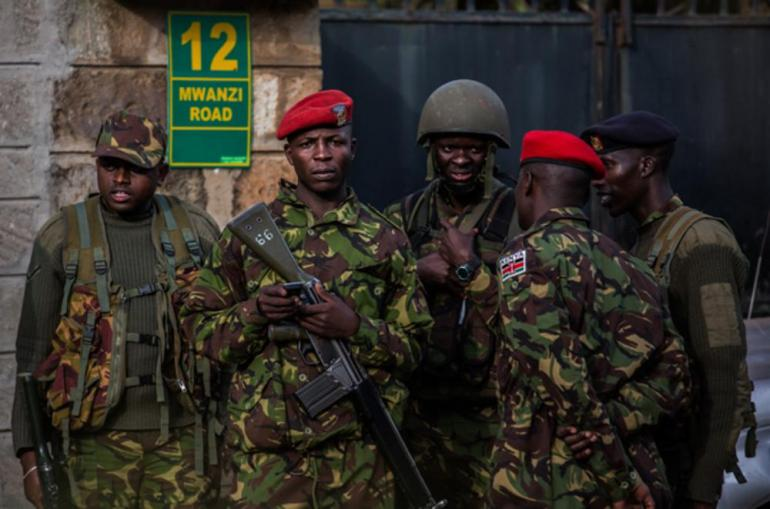 Kenyan soldiers wait for orders outside the Westgate shopping centre, 24 hours after the the attack began. A stalemate developed between the armed attackers inside and the Kenyan police and military forces outside.