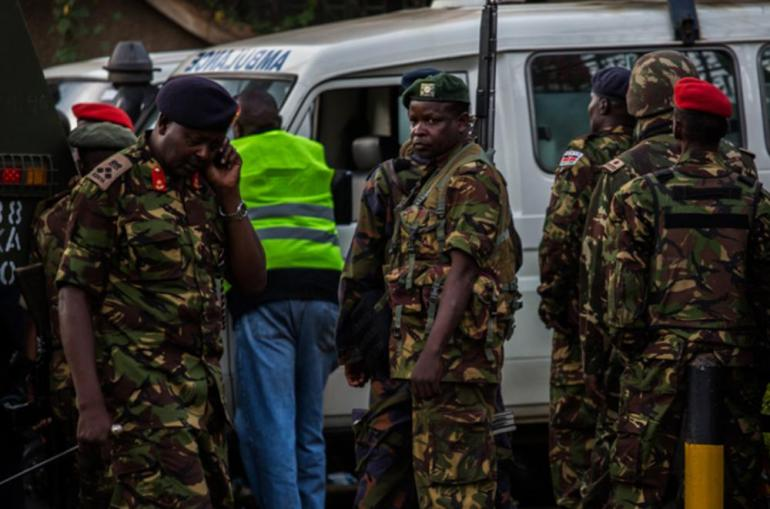 Kenyan military personnel watch and wait as their fellow soldiers move into the Westgate shopping centre complex at around 5pm on Sunday. Chain of command issues and poor communication between police and military were said to have delayed the counter-attack.