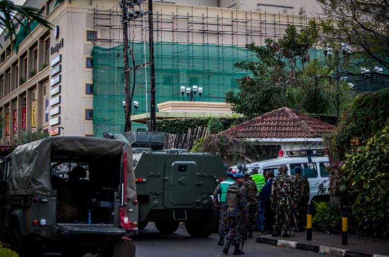 Police and Kenyan military personnel surround the building as forces move into position for an assault against al-Shabab, the armed group which took shoppers hostage on Saturday.