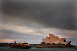 Ferries sail past the Sydney Opera House as smoke from bushfires can be seen above.