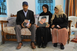 Family members hold pictures of Walid Denguir, 32, who died in police custody [Aymen Ben Mansour/Al Jazeera]