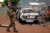 French troops patrol past two Seleka vehicles set on fire by Christian mobs in Bangui, Central African Republic, Monday Dec. 9, 2013. Both Christian and Muslim mobs went on lynching sprees as French Forces deployed in the capital. At least one Seleka suspect was stoned to death by the crowds. (AP Photo/Jerome Delay)