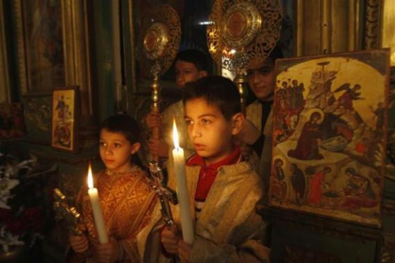 Palestinian Christian boys hold candles during a service in the Saint Porfirios church in Gaza City on Christmas day [Reuters]
