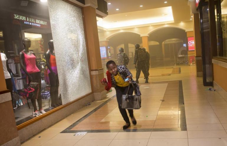 A woman who had been hiding during the gun battle runs for cover after armed police enter the Westgate Mall in Nairobi, Kenya, after gunmen threw grenades and opened fire.