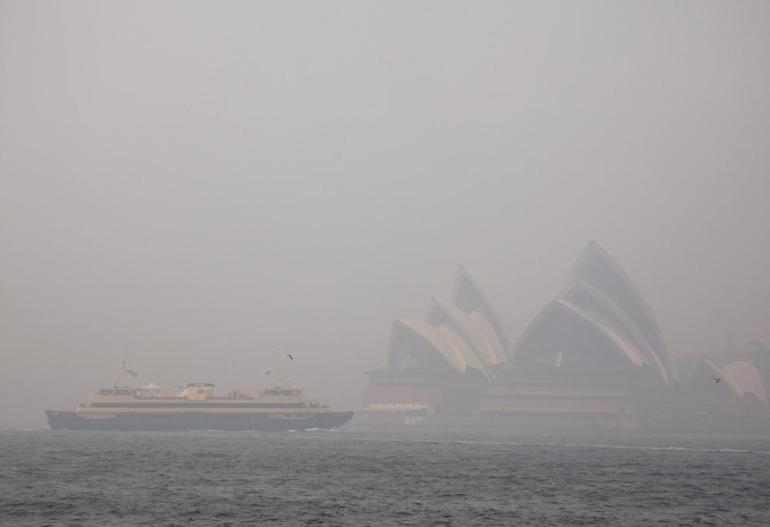 A ferry passes the Sydney Opera House as thick smoke from bushfires blanketed the city November 2, 2013.
