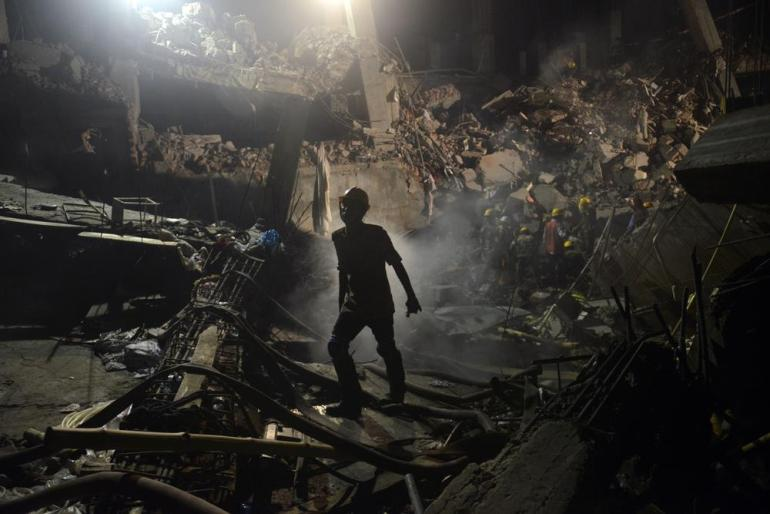 A worker leaves the site where a garment factory building collapsed near Dhaka, Bangladesh killing 1,129 people.
