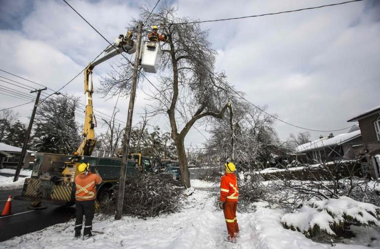 Toronto employees work to restore power  following an ice storm in Canada(***)s largest city, December 27. Over 30,000 residents have been left without power since the storm hit on December 22.