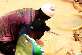 Pa Abou Conde and his son search through gravel for diamonds.