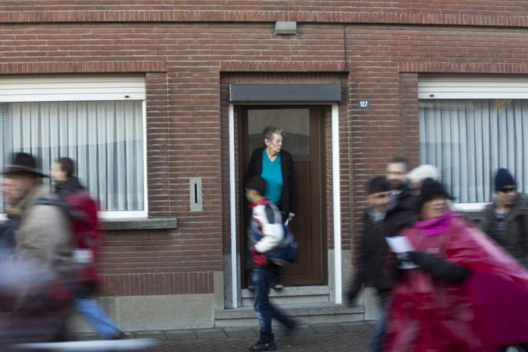 A Belgian woman looked outside as the march passed in front of her home.
