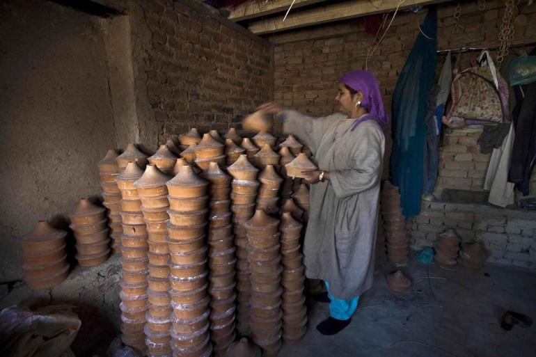 A woman stacking dried earthen pots.
