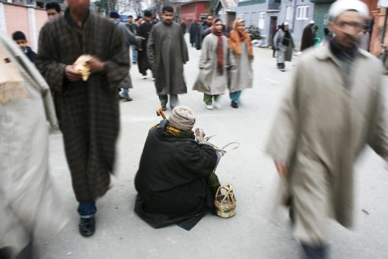 A beggar seeking alms with kangri on his side in Srinagar.