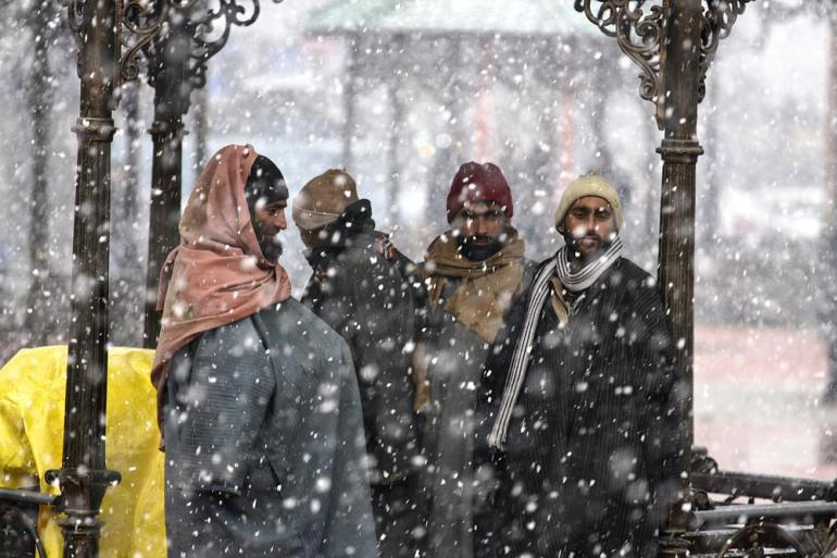 Kashmiri men keep themselves warm with kangri during heavy snowfall in Srinagar.