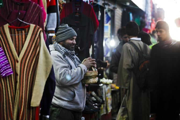 A local trader warms himself with kangri outside his shop in Srinagar.
