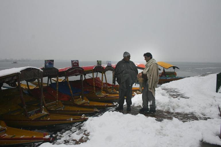 Kashmiri boatmen keep themselves warm with kangri after heavy snowfall at Dal lake in Srinagar.