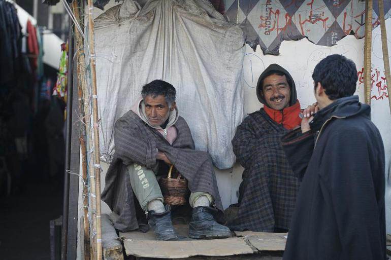 Drivers keep themselves warm with kangri at a bus stand in Srinagar.