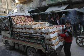 A child stands beside a stock of pomegranates he sells in Aleppo, stuck with a surplus because so many people have fled the once-bustling commercial capital.